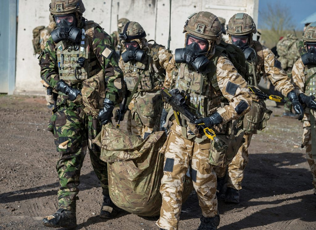 A team of Commando Royal Marines is protective gear and gas masks