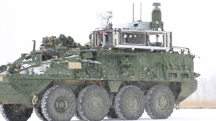 Wheeled military vehicle in the snow with mounted sensors on top for chemical detection