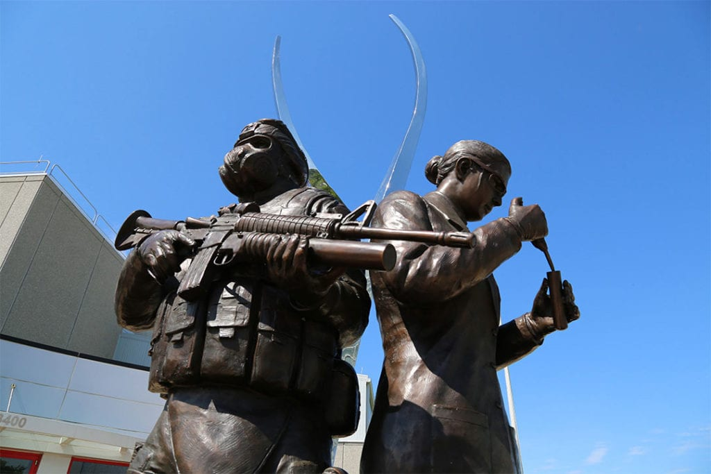 Bronze statue of solider in gas mask standing back to back with a scientist pipetting into a test tube. Statue is outside building against a backdrop of blue sky.