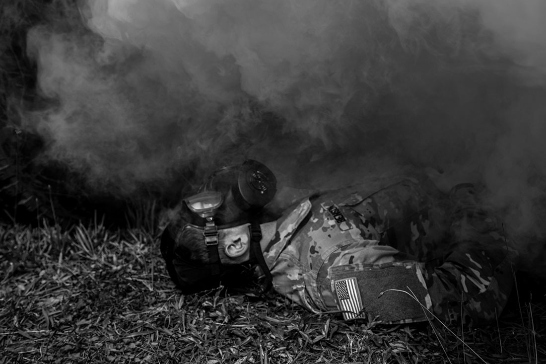 Soldier with gas mask enveloped by yellow cloud of simulated chemical weapon