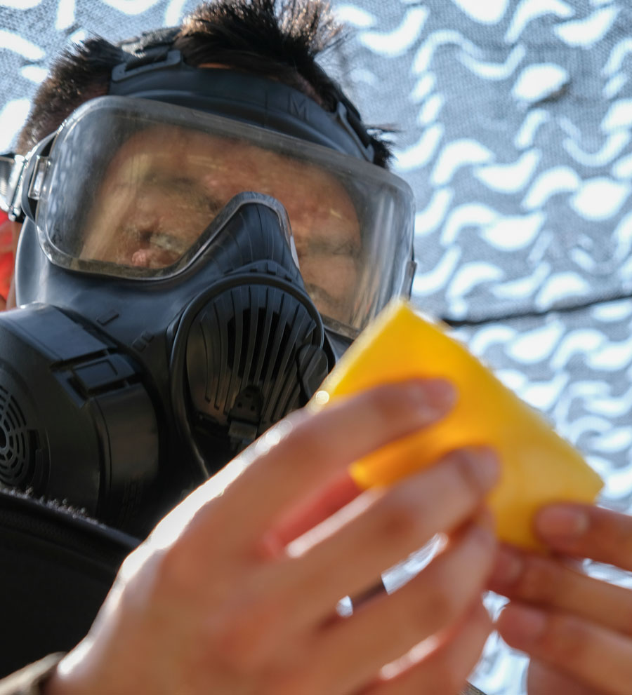Close up of soldier in gas mask holding yellow sponge applicator