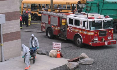 Scene of disaster triage with fire truck, schoolbus and first responders in hazmat suits with patients