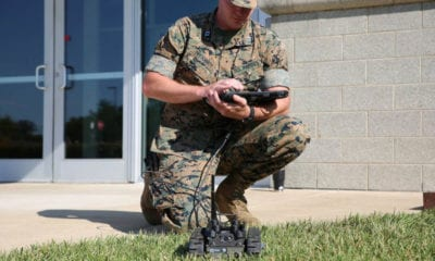 Marine in camouflage uniform kneels cradling controller board to operate small robot in front of him in the grass