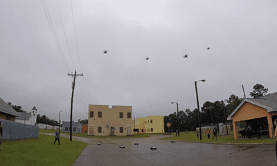 A swarm of small airborne drones over an urban street
