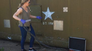 Gloved chemist stands outside large green metal army bunker with hose-like device attached to sensor in metal case