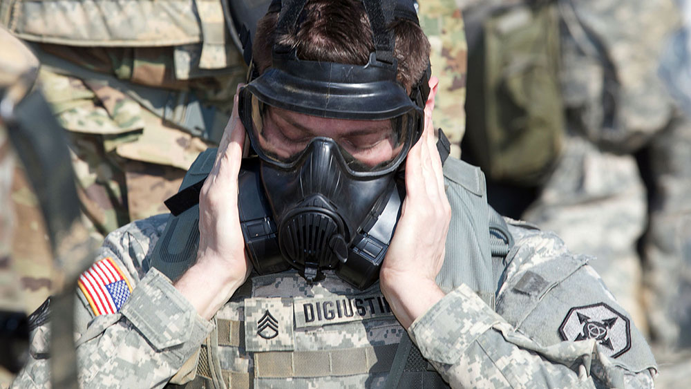 Soldier dons gas mask