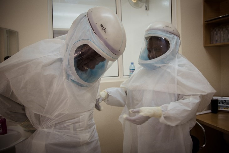 Health care workers in protective suits