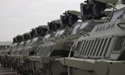 parked mine-resistant vehicles lined up