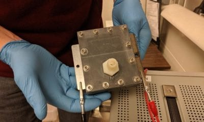 metal flow cell box held by gloved hands in laboratory setting