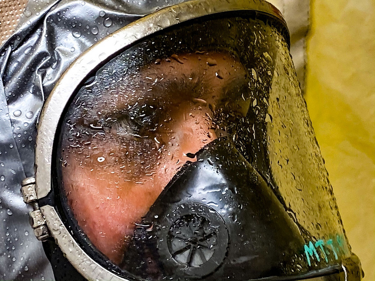 Focused look on face of soldier seen through mask covered in water droplets