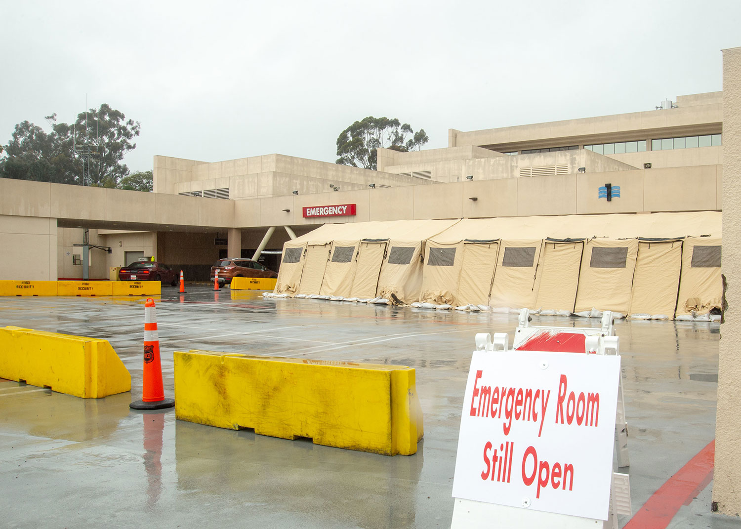 Large triage tent outside emergency entrance to hospital