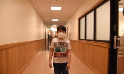 Young boy walks hallway wearing mask in video intro